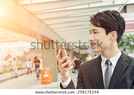 Confident young Asian businessman using cellphone, concept of business, technology, social media etc. - stock photo