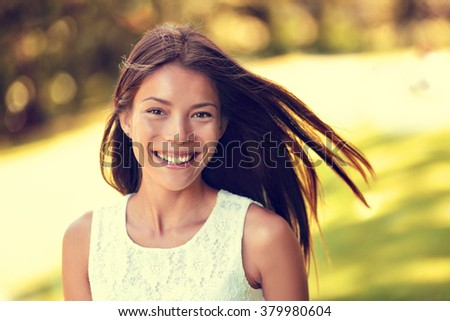 Confident young Asian Chinese beauty woman smiling. Beautiful portrait of healthy female adult in sunny summer grass park background for spring, summertime or pollen allergy season concept. - stock photo