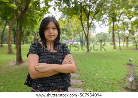 Confident young Asian woman in park with arms crossed