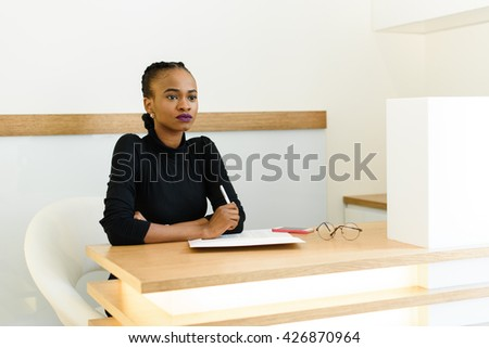 Confident young black business woman holding pen and thinking at desk in office - stock photo