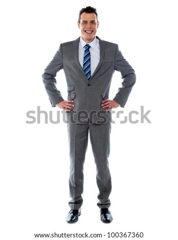 Confident young business executive posing with hands on his waist, studio shot - stock photo