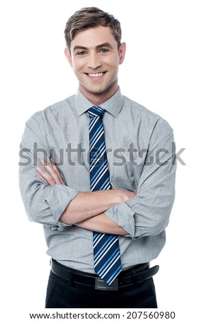 Confident young business executive with crossed arms  - stock photo