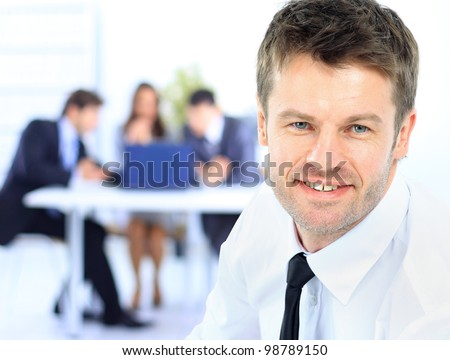 Confident young business man attending a meeting with his colleagues - stock photo