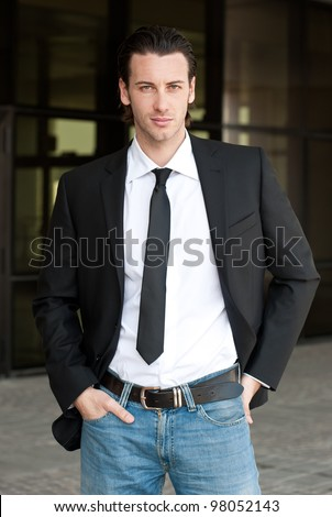 Confident young business man looking at camera. Dark background.