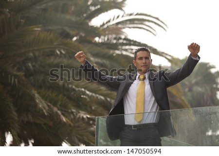 Confident young businessman at his office balcony - stock photo