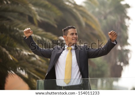 Confident young businessman at his office balcony