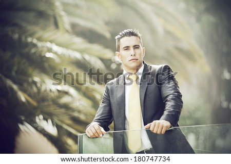 Confident young businessman at his office balcony (with backlight) - stock photo