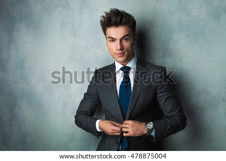 confident young businessman buttoning his suit  on studio background