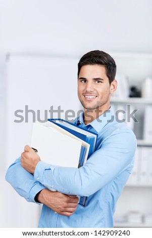Confident young businessman carrying binders in office