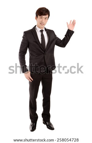 Confident young businessman in formalwear pointing or show something isolated on white.
