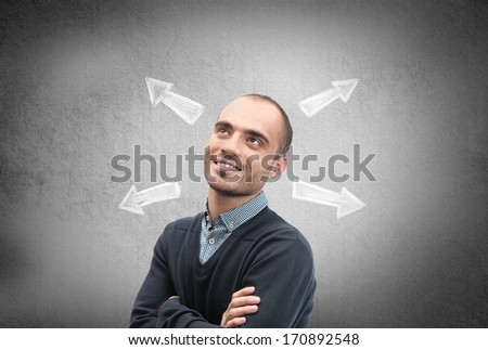 Confident, young businessman looking at chalk drawn arrows on a concrete wall - stock photo