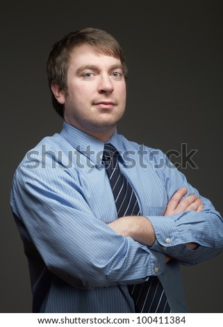 Confident young businessman on dark background - stock photo