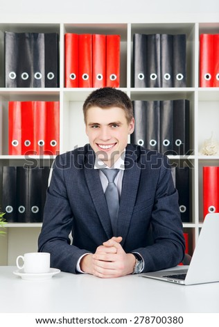 confident young businessman sitting at table in his office - stock photo