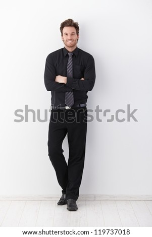 Confident young businessman smiling arms crossed, leaning to wall. - stock photo
