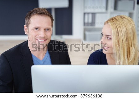 Confident young businessman with a friendly smile working together with a female colleague on a computer in the office - stock photo