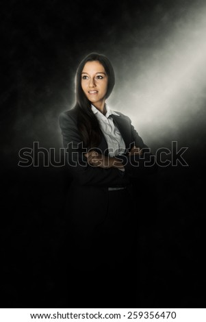 Confident Young Businesswoman Crossing her Arms Over her Stomach Illuminated with Light From the Upper Right Corner of the Frame on a Black Background While Looking to the Left. - stock photo