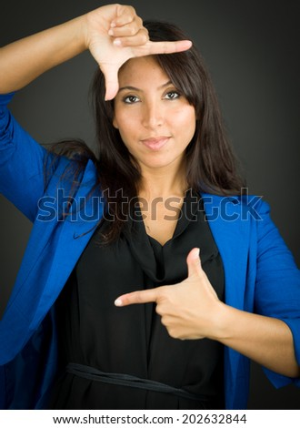 Confident young businesswoman making frame with fingers