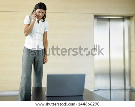 Confident young businesswoman on call looking at laptop in office lobby