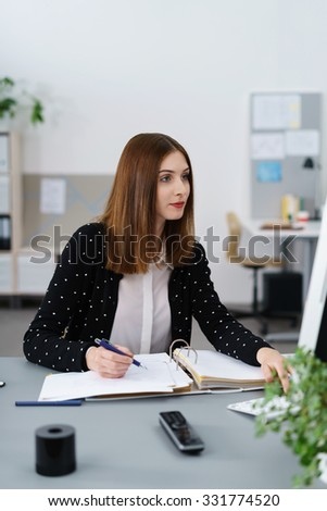 confident young businesswoman taking notes while looking at computer - stock photo
