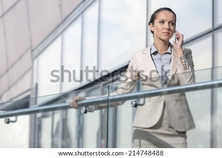 Confident young businesswoman using cell phone at office balcony - stock photo
