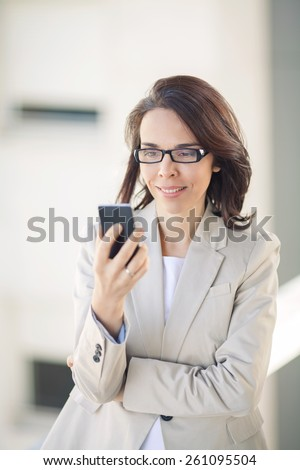 Confident young businesswoman using mobile phone. - stock photo