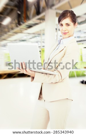 Confident young businesswoman with laptop against classroom - stock photo