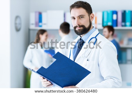 Confident young doctor posing in the office, he is smiling at camera and holding medical records, medical team on the background - stock photo