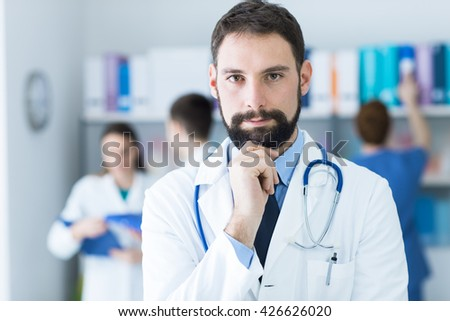 Confident young doctor posing in the office, he is smiling at camera with hand on chin, medical team on the background - stock photo