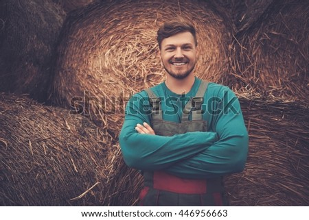 Confident young farmer standing near haystacks in his farm.