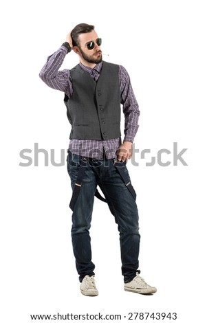 Confident young fashionable man smoking cigarette looking away. Full body length portrait isolated over white background.