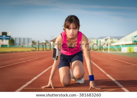 Confident young female athlete in starting position ready to start a sprint. Female jogging. Woman jogging on sunset. Woman running on a running track. running shoes. Woman running and jogging concept - stock photo