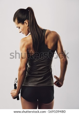 Confident young female athlete with jumping rope posing on grey background. Rear view of woman bodybuilder back standing holding skipping rope. - stock photo