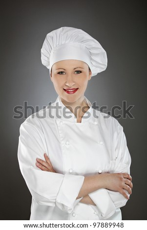 Confident young female chef with arms crossed - stock photo