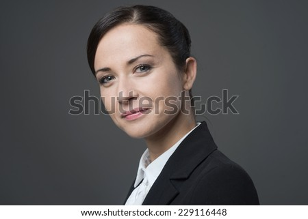 Confident young female manager smiling at camera, posing on gray background. - stock photo