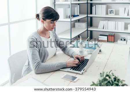 Confident young freelancer sitting at office desk and working with a laptop, efficiency and entrepreneurship concept