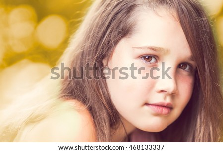 Confident young girl looking at camera smiling on a sunny day with beautiful background