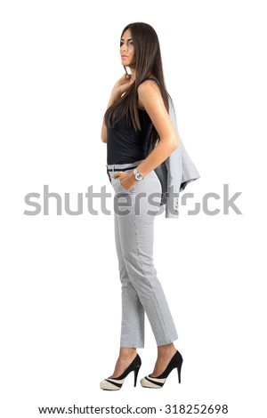 Confident young gorgeous business woman in formal suit holding jacket over the shoulder. Full body length portrait isolated over white studio background.
