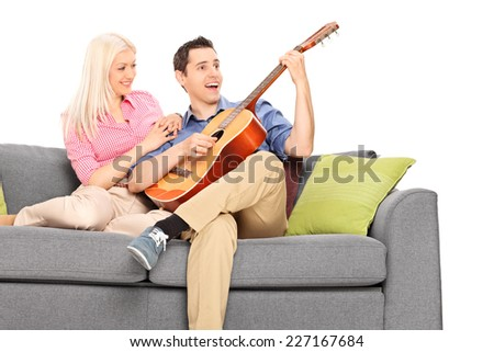 Confident young guy playing guitar with his girlfriend seated on sofa isolated on white background - stock photo