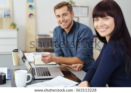 Confident young male business manager in a meeting with a female colleague sitting together at a desk discussing information on a laptop computer