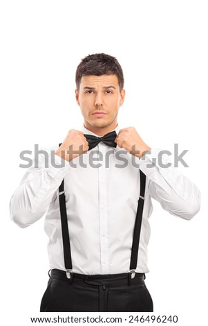 Confident young man adjusting his bow-tie isolated on white background