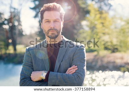Confident young man close up portrait outdoor in a park. Flare light effect. - stock photo
