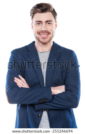 Confident young man. Handsome young man keeping arms crossed and smiling while standing against white background - stock photo