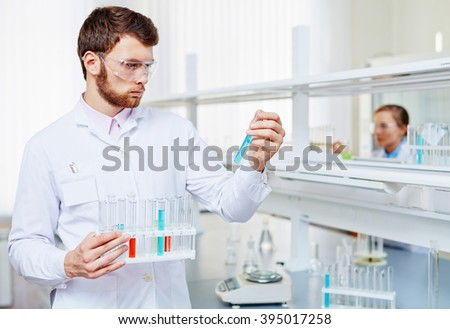 Confident young man in protective eyewear holding test tube with blue liquid - stock photo