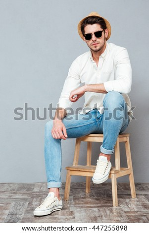 Confident young man in white shirt, hat and sunglasses sitting and posing over grey background - stock photo