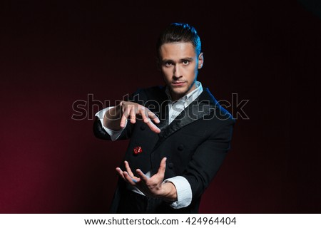 Confident young man magician showing tricks using one flying dice over dark background - stock photo
