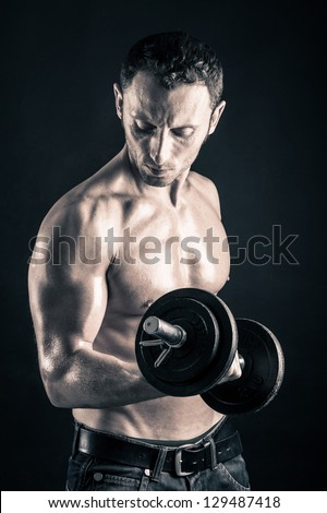 Confident young man shirtless portrait training with dumb-bell against black background. - stock photo