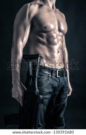 Confident young man shirtless portrait with machine gun against black background. - stock photo