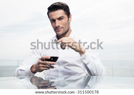 Confident young man standing with glass of wine outdoors and looking at camera - stock photo