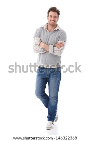Confident young man wearing jeans and shirt standing arms crossed, smiling. - stock photo