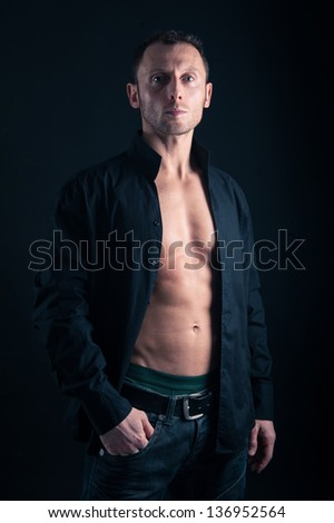 Confident young man with open shirt portrait against black background. - stock photo